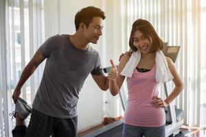 dois adultos exercitando na academia foto
