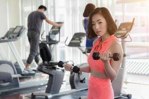 mulher asiática exercitando na academia foto