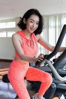 mulher asiática, exercitando-se no ginásio