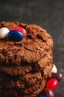 biscoitos de chocolate empilhados no plano de fundo texturizado preto escuro foto