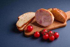 fatias de carne, tomate e pão na tábua de madeira foto
