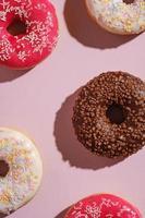 donuts de chocolate, rosa e baunilha com granulado em fundo rosa