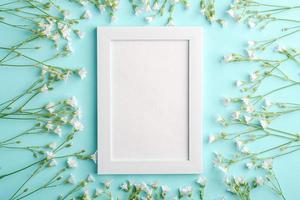 maquete de moldura branca vazia com flores de morrião dos passarinhos em fundo azul