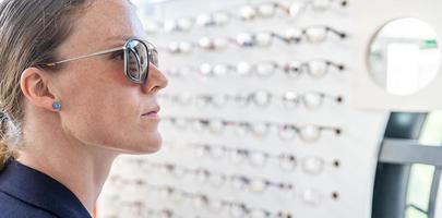 mulher escolhe um par de óculos