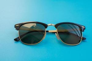 óculos de sol em fundo azul foto