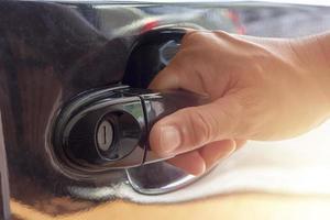close-up de mão abrindo a porta do carro foto