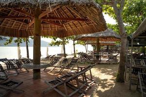 espreguiçadeiras de praia sob cabana foto
