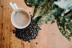 grãos de café e caneca na mesa de madeira foto