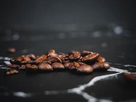 grãos de café na superfície de mármore preto foto