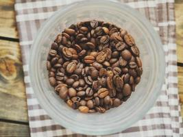 grãos de café em copo de plástico foto