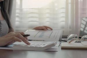close-up da mulher que trabalha na calculadora no escritório em casa foto
