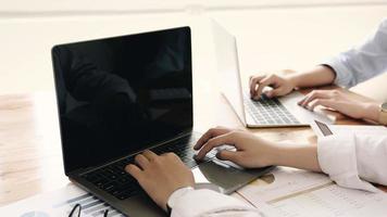 duas pessoas trabalhando em laptops foto