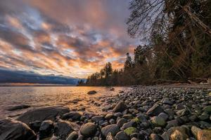 costa rochosa ao pôr do sol foto