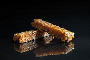 barras de granola em fundo preto foto