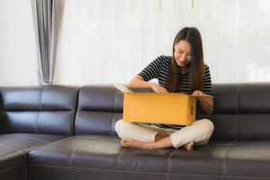 mulher abrindo a caixa de papelão no sofá foto