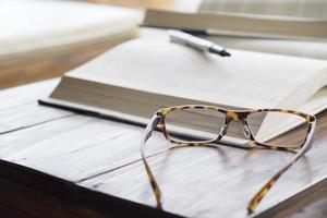 close-up de óculos de leitura ao lado do livro