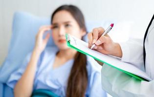 close-up de médico feminino asiático no trabalho com o paciente foto
