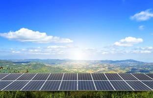 um campo de painel solar de energia fica no topo de uma montanha sob o céu azul