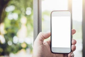 homem segurando o telefone inteligente com tela em branco