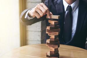 homem construindo torre de bloco de madeira