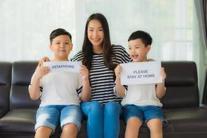 mãe com dois filhos segurando cartazes para ficar em casa foto