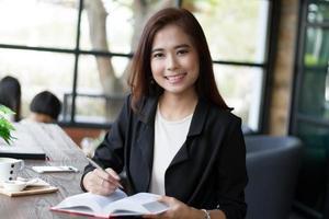 empresária asiática sorrindo segurando livro e caneta foto