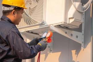 O técnico está verificando a unidade de ar condicionado externo, medindo o equipamento para encher os aparelhos de ar condicionado.