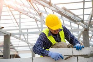 construtor está aplicando gesso em uma parede de tijolos foto