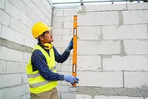 O engenheiro mede os blocos de concreto leves da parede com um nível no canteiro de obras.
