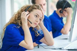 trabalhadores estressados do call center na frente dos computadores foto
