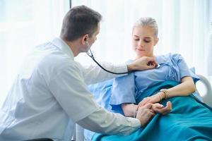 médico homem tomando o pulso do paciente do sexo feminino foto