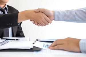 duas pessoas apertam as mãos sobre documentos foto