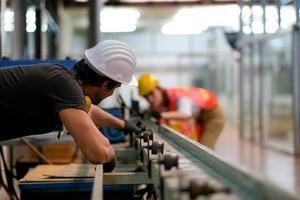 técnico masculino na planta industrial, trabalhando ao lado do colega de trabalho feminino foto