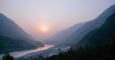 pôr do sol nevoento sobre o rio indus foto
