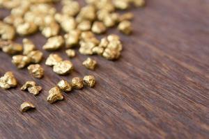 pepitas de ouro sobre fundo de madeira foto