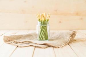 varas de biscoito coberto de chá verde matcha em frasco de vidro