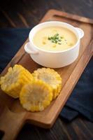 sopa de milho com milho lateral no prato de madeira foto