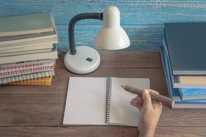 local de trabalho com lâmpada de leitura e livros na mesa de madeira velha foto