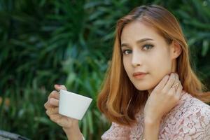 mulher tomando café lá fora foto