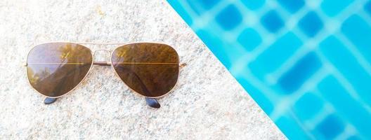 vista superior vista de óculos de sol à beira da piscina foto