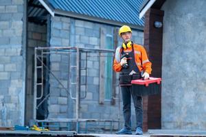 trabalhador da construção civil segurando broca e caixa de ferramentas foto