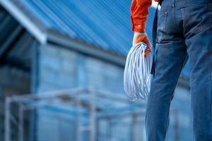 trabalhador, segurando a corda na frente do canteiro de obras