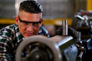 engenheiro com óculos de proteção, trabalhando na fábrica