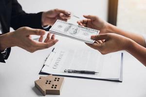 agente imobiliário dando dinheiro ao comprador de imóvel residencial foto