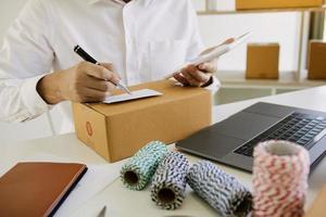 jovem macho preparando pacote nos correios foto