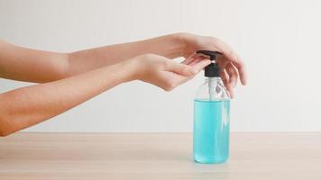jovem mulher asiática usando álcool gel desinfetante para as mãos.