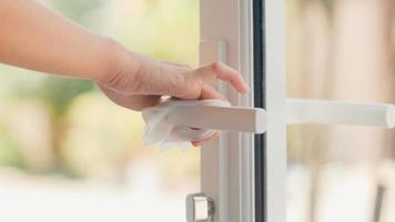 mulher asiática usando spray de álcool na maçaneta da porta em casa foto