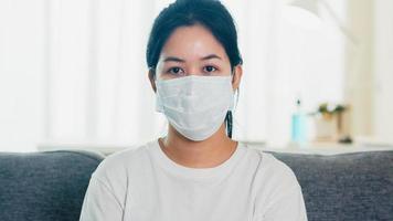 mulher asiática usando máscara protetora, sentado no sofá.