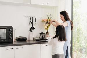 jovem mãe japonesa asiática e filha cozinhando em casa