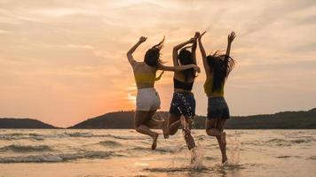 grupo de três jovens mulheres asiáticas pulando na praia.
